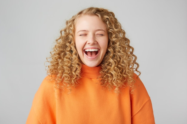 Resilient happy cheerful curly-haired blonde closed her eyes with pleasure, enjoys the moment laughing, wearing a warm orange oversize sweater