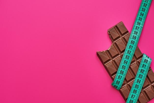 誘惑に抵抗する。ピンクの背景に分離されたメジャーテープで包まれたチョコレートバー