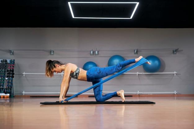 脚のトレーニングロバキックフロアエクササイズをしているレジスタンスバンドフィットネス女性。キックバックによる臀筋の活性化。