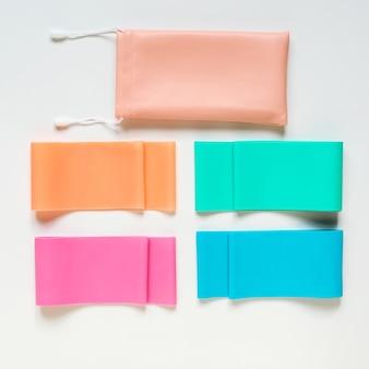 Разноцветные полосы сопротивления и сумка для хранения на белом фоне, витрина с оборудованием для фитнеса или тренировок, плоский вид сверху