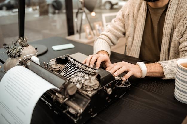 Решительный старомодный мужчина. сосредоточенный красавец в сером домашнем кардигане печатает римский текст на антикварной пишущей машинке