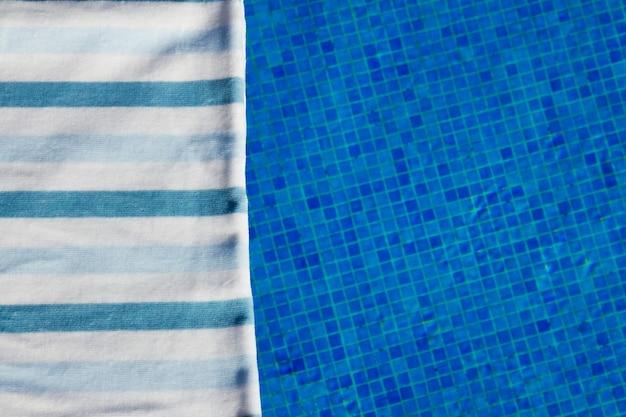 Курортный фон с полосатым полотенцем возле бассейна