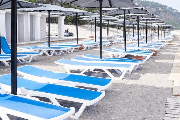 空のサンラウンジャーのあるリゾートビーチ。海での休暇。サンラウンジャー