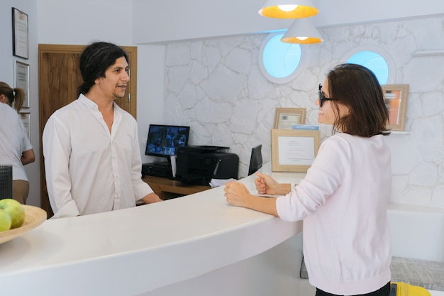 Resort hotel front desk, woman guest talking to man working at reception