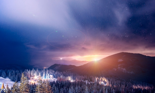 The resort ski resort illuminated at night is located in a picturesque place above a clear starry sky. country vacation concept.