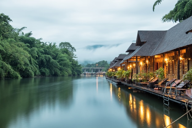 Resort wooden house floating and mountain fog on river kwai
