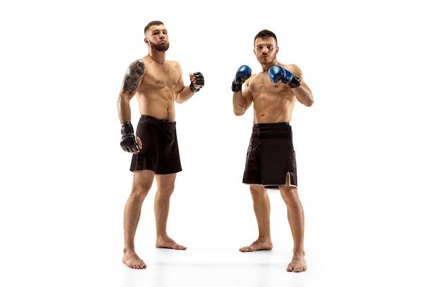 Уважение к оппоненту. два профессиональных бойца позирует на белом фоне студии. пара подходящих мускулистых кавказских спортсменов или борющихся боксеров. спорт, конкуренция, концепция эмоций.