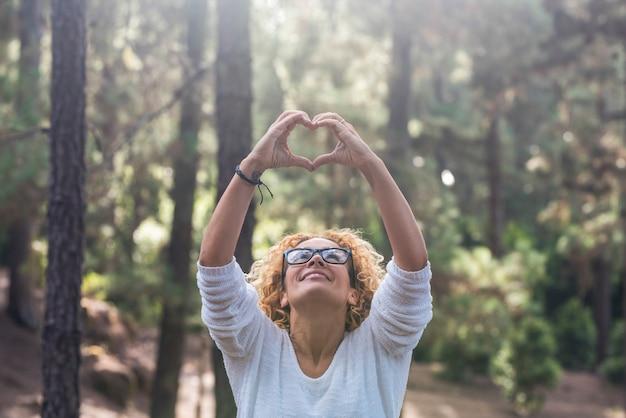 屋外の自然を尊重し、美しい大人の女性が上を見上げ、両手で囲炉裏の愛のサインをすることで、森の世界のコンセプトを守る