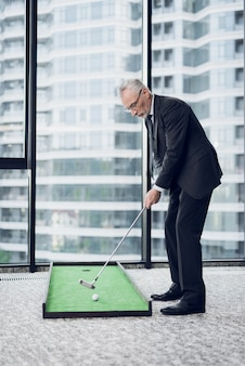 A respectable elderly man playing a mini golf in the office.