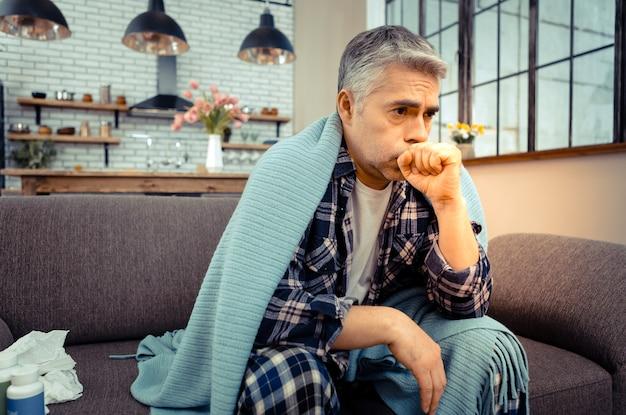 呼吸器疾患。強い咳をしながら自宅のソファに座っている不幸な病人