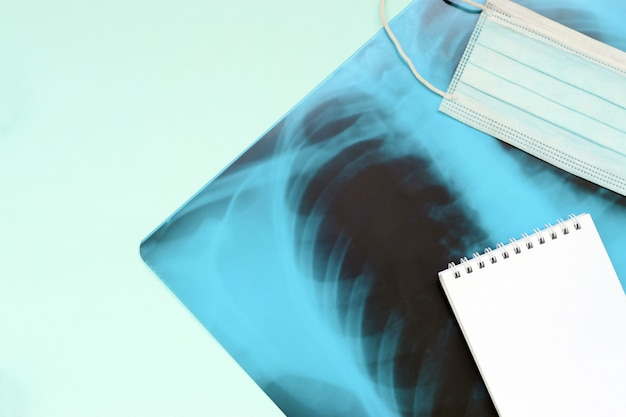 Respiratory mask and empty notepad page on x-ray of human lungs, top view