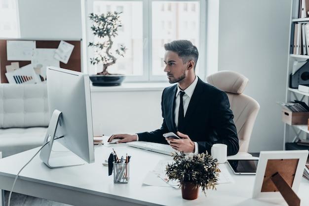 電子メールで応答します。スマートフォンを保持し、コンピューターを使用して作業する正装の真面目な青年