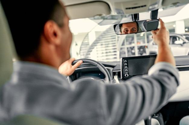 책임있는 백인 자동차 운전자가 백미러를 이동합니다. 뒷좌석에서 찍은 사진.