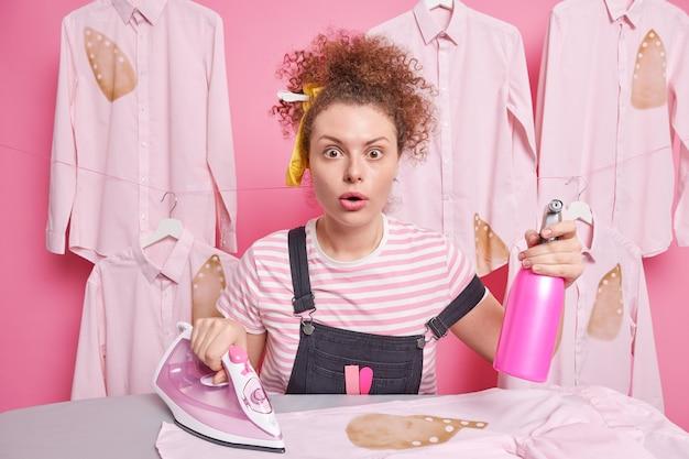 Ответственная кудрявая горничная смотрит с упорными глазами, занята работой по дому, стоит возле гладильного стола, держит бутылку с распылителем воды и стоит электрический утюг возле выглаженных рубашек. концепция домашнего хозяйства