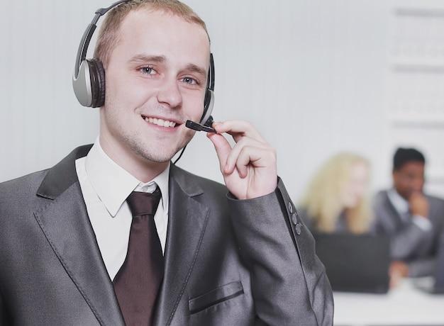 オフィスの背景にヘッドセットを備えた責任ある従業員のコールセンター