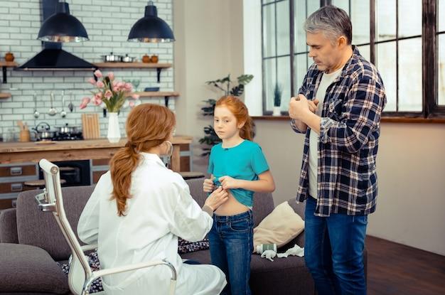 책임감있는 아버지. 그의 딸의 건강에 대해 걱정하면서 의사를 부르는 심각한 성숙한 남자