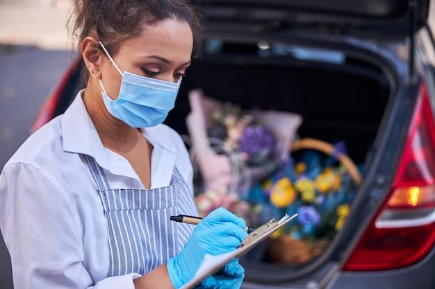 꽃다발 배달에 대해 메모하는 책임 있는 여성 꽃집