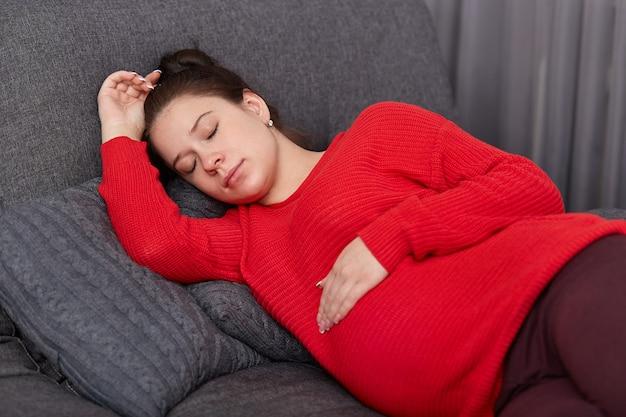 휴식과 pregancy 개념. 갈색 머리 임신 예쁜 여자는 오후에 낮잠을하고, 캐주얼 옷을 입고, 배에 손을 보유