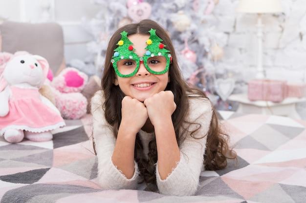 休んでリラックスしてください。クリスマス・イブ。家のクリスマス休暇で小さな女の子。のんきな子供時代。冬休み。寝室でリラックスした子供。愛らしい少女はクリスマスツリーのメガネの写真ブースの小道具を着用します。