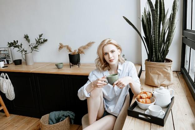 Отдых на дому концепции. молодая красивая женщина завтракает дома в яркой стильной кухне у окна.
