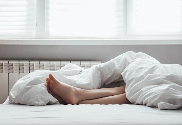 집에서 쉬다. 여성 다리. 여자는 흰색 담요 아래 침대에 누워 있습니다.