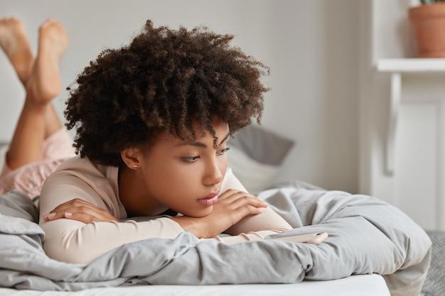 휴식의 날과 휴식 개념. 잠옷에 잠겨있는 꿈결 같은 어두운 피부의 여성, 침대에 누워, 편안함을 즐기고, 깨어 난 후 무언가에 대한 꿈을 꾸고, 가정적인 분위기를 즐기고, 외로움을 느낍니다.