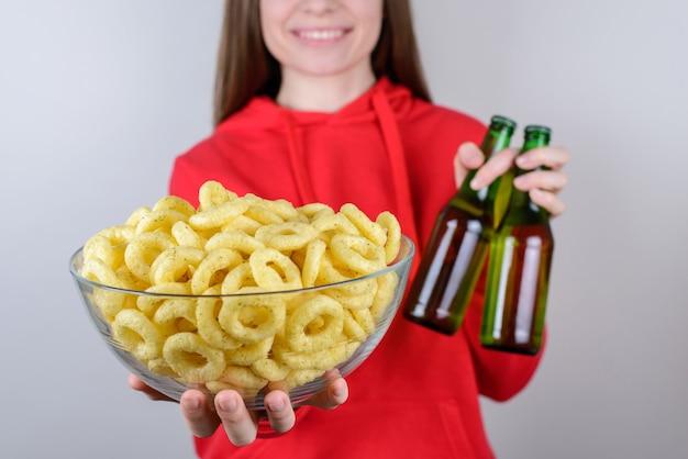 나머지는 진정 알코올 개념을 진정시킵니다. 잘린 근접 촬영 평온한 부주의 한 긍정적 인 기쁜 좋은 여자는 전체 큰 큰 쌀 반지를 손에 들고 두 병 고립 된 회색 배경