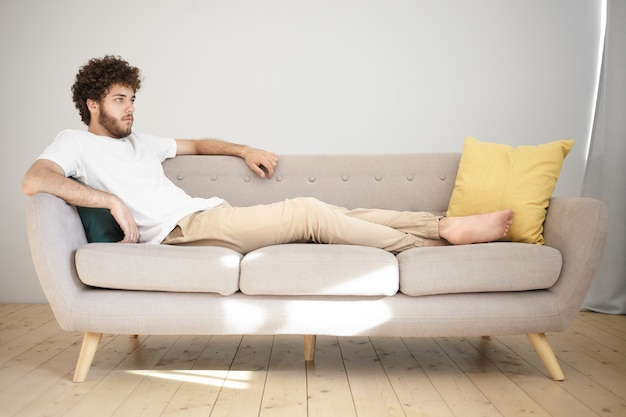 Отдых, релаксация и концепция досуга. привлекательный молодой человек с щетиной и пышными волосами удобно лежит на сером диване в гостиной и смотрит телевизор, наслаждаясь футбольным матчем или сериалом