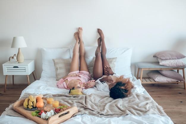 休息、リラクゼーション。自宅の寝室で足を上げてベッドで休んで横たわっているランジェリーの若い大人の細いガールフレンド