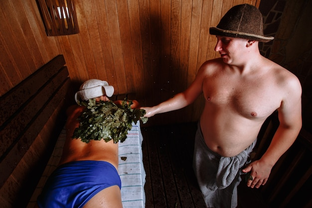 Rest in the sauna. the bath attendant hovers over the client's oak broom
