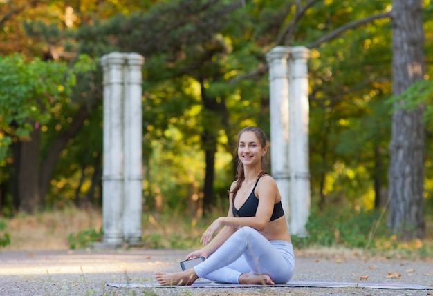 Rest and workout concept. young fit woman sitting on yoga mat in the park and looking smiling at camera
