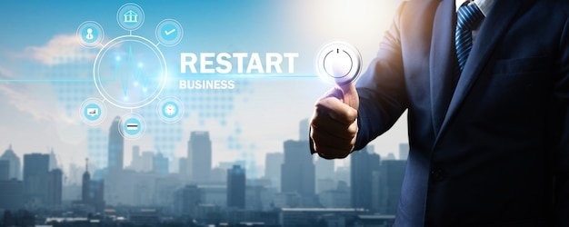 Restart business and back to work and normal working campaign, thumb of businessman press on start button icon on town and city background