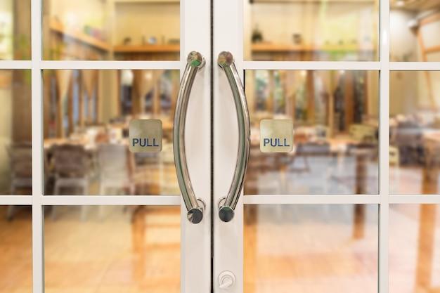 Дверная ручка ресторана с надписью на стеклянных дверях