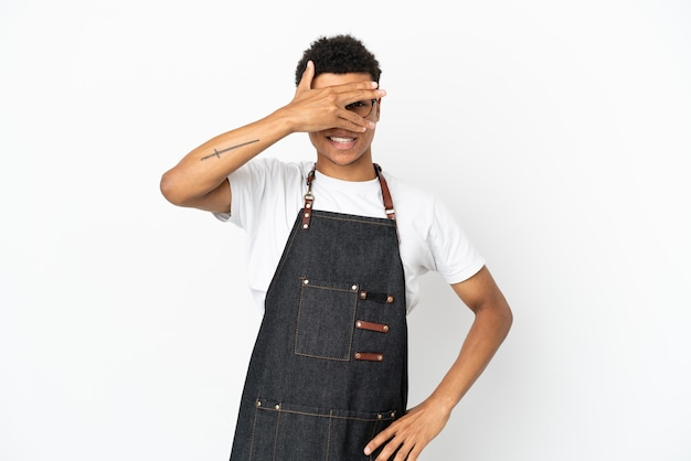 Ресторан афро-американских официант мужчина изолирован на белом фоне, закрывая глаза руками и улыбаясь