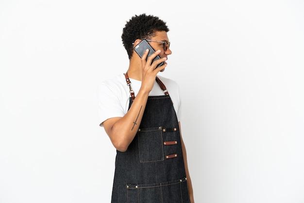 Ресторан афро-американский официант, изолированные на белом фоне, разговаривает с кем-то по мобильному телефону