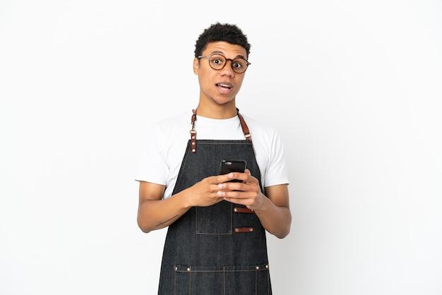 白い背景で隔離のレストランアフリカ系アメリカ人ウェイター男は驚いてメッセージを送信します