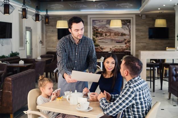 レストランと休日のコンセプトです。ウェイターがカフェで幸せな家族にメニューを与える