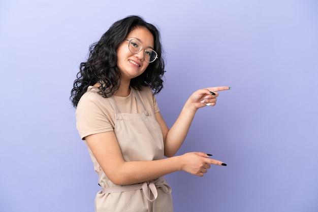 Азиатский официант ресторана изолирован на фиолетовом фоне, указывая пальцем в сторону и представляет продукт