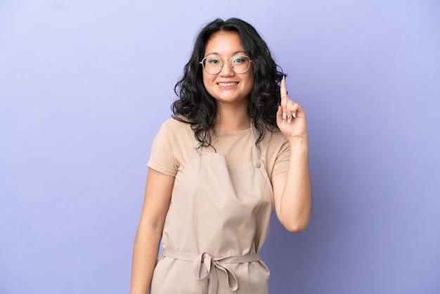 Азиатский официант ресторана изолирован на фиолетовом фоне, показывая и поднимая палец в знак лучшего