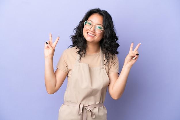 Азиатский официант ресторана изолирован на фиолетовом фоне, показывая знак победы обеими руками