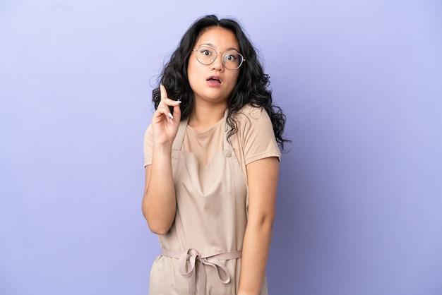 指を上に向けるアイデアを考えて紫色の背景に分離されたレストランアジアのウェイター