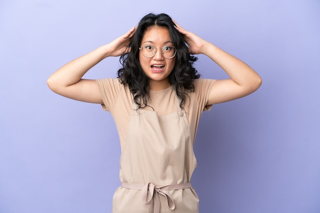 Restaurant asian waiter isolated on purple background with surprise expression