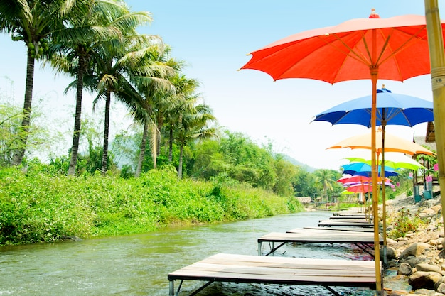 Restaurant by the river and decorated with colorful umbrella. thailand.