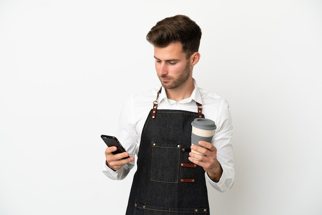 흰색 배경에 격리된 백인 레스토랑 웨이터는 테이크아웃 커피와 모바일을 들고 있습니다.