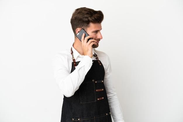 Кавказский официант ресторана изолирован на белом фоне, ведя разговор по мобильному телефону с кем-то