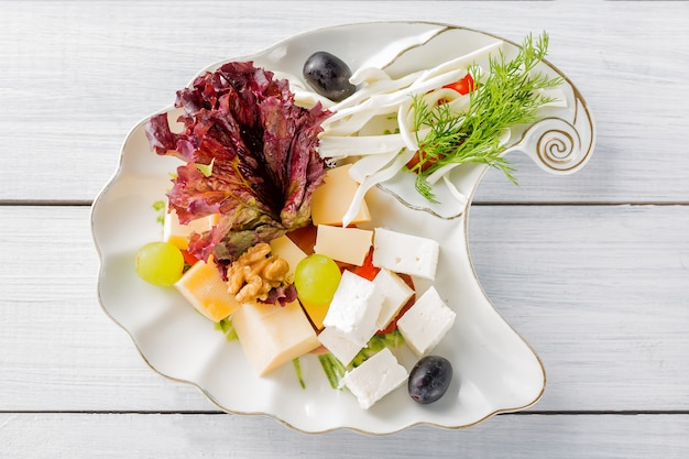 Restaurant cheese plate various types of cheeses with grapes and black olive on white plate