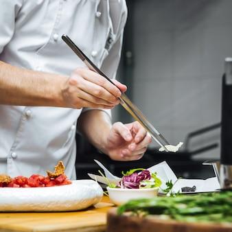 Шеф-повар ресторана готовит карпаччо из говяжьей вырезки с пармезаном и рукколой