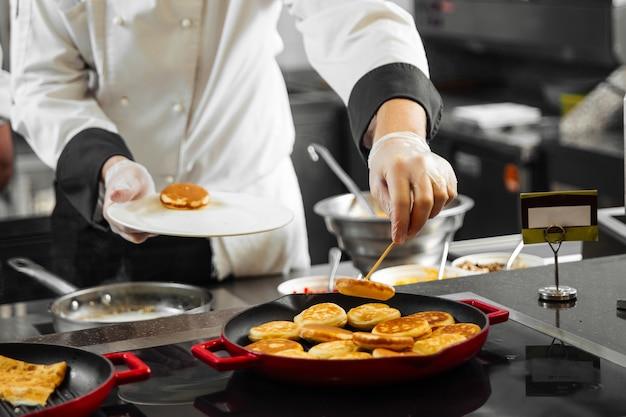 Шеф-повар ресторана готовит блины на кухне