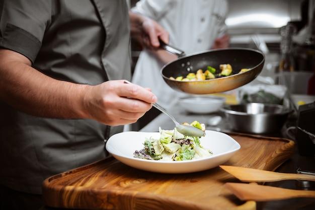 Шеф-повар ресторана готовит теплый салат с листьями салата