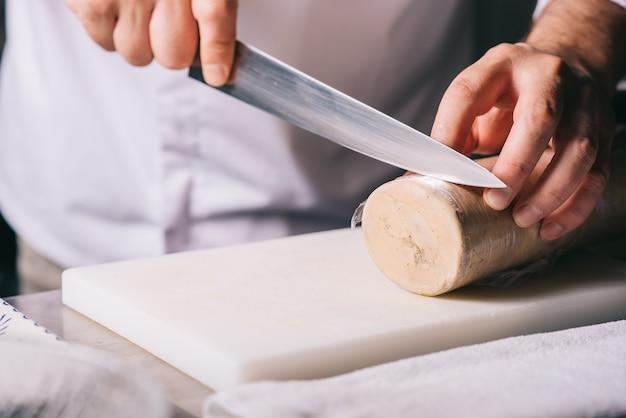 Шеф-повар ресторана нарезает фуа-гра